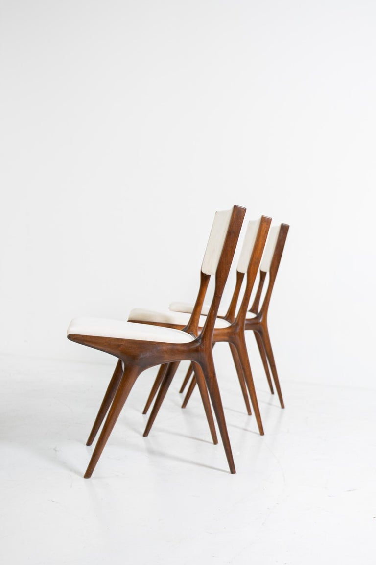 Rare and beautiful set of 6 chairs Carlo de Carli model 158 for Cassina. The chairs are made of Italian walnut. The backrest and seat have been upholstered in white velvet fabric. The particularity of the chairs is the protruding ashlar on the