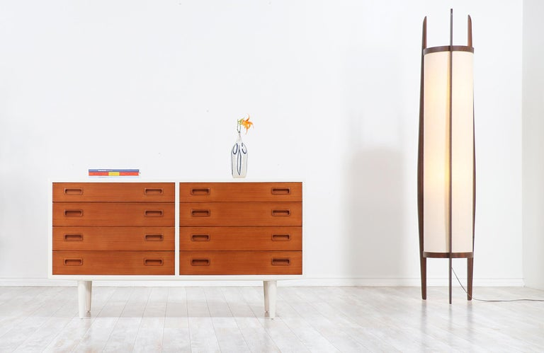 Beautiful modern dresser designed by Carlo Jensen for Hundevad & Co. in Denmark, circa 1960s. This stylish design features a smooth hand-polished white lacquered wood case and eight spacious dovetailed drawers in teak wood with rectangular recessed