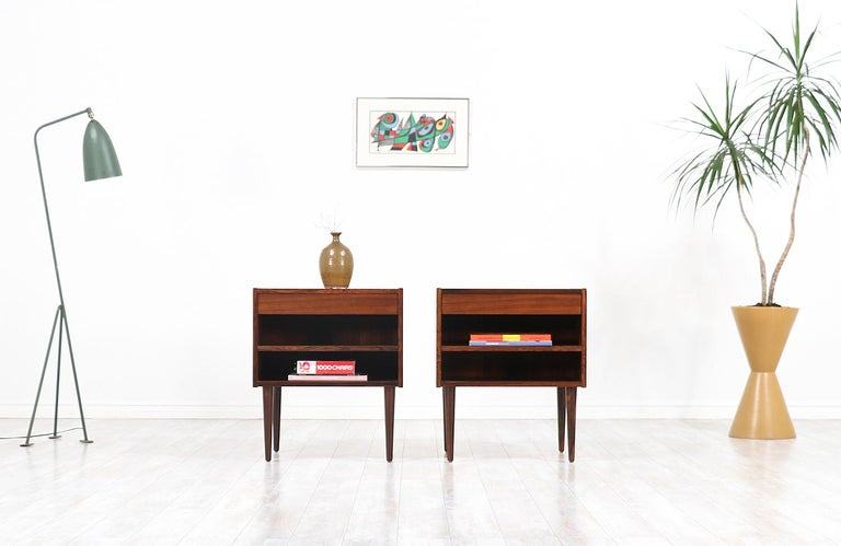 A pair of stylish modern nightstands designed by Carlo Jensen and manufactured by Hundevad & Co. In Denmark, circa 1960s. This unique pair features a Brazilian rosewood construction with a dovetailed drawer on top and an adjustable lower shelf ideal
