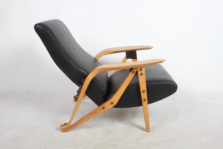 Produced by Zanotto, Italy from drawings by Carlo Mollino from 1954. The production of this Gilda chair dates from the late 1980s-1990s. Ash dyed frame with black leather upholstery and bronze hardware. The Gilda chairs lines are both sexy and