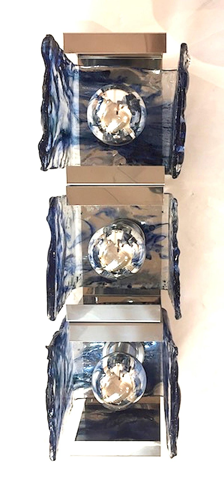 A beautiful and architectural pair of chrome mount and glass shade sconces by Carlo Nason for well known Italian lighting company Mazzega. Three hand formed clear with blue glass square