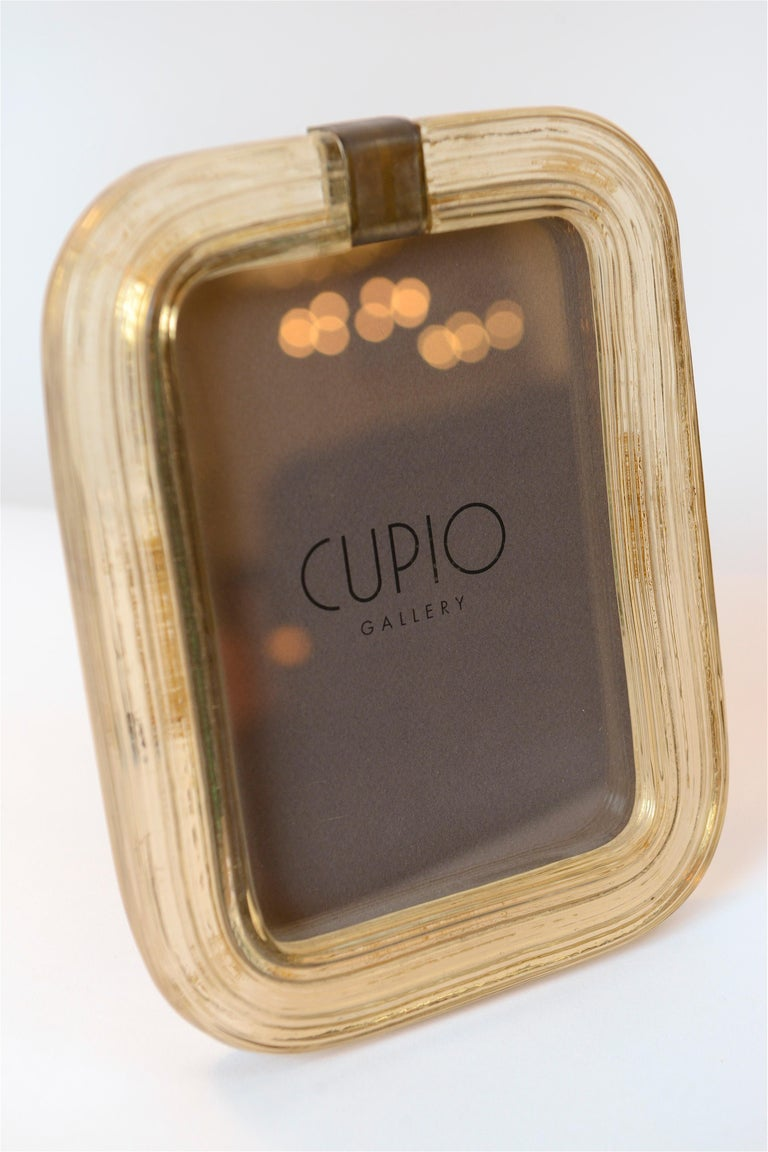 A particularly beautiful 1940s picture frame designed by Italian architect and designer Carlo Scarpa. Produced by the prestigious Muranese Company, Venini, this honey colored piece was made using the 'Battuto' glass making technique. Deep vertical