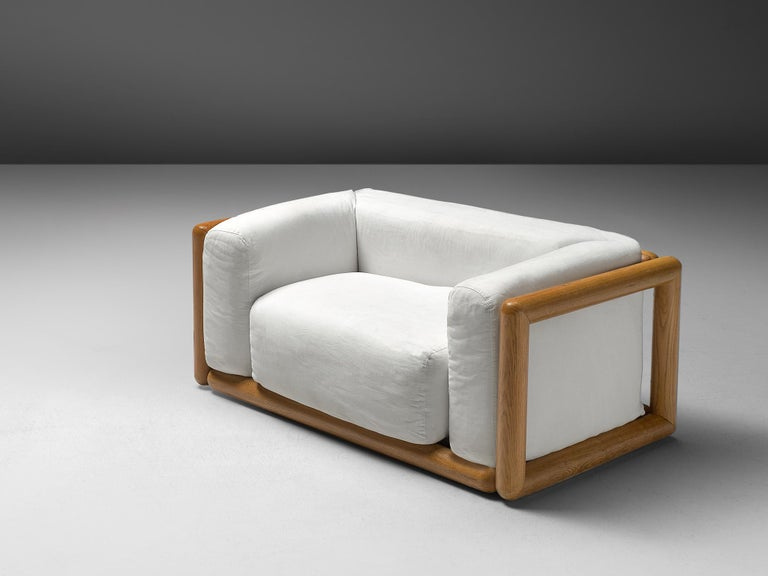 Carlo Scarpa for Simon, 'Cornaro' lounge chairs, white fabric, ash, Italy, 1973  This loveseat has a very thick cushion and is upholstered with white fabric. The lounge chair have a relatively thin back and armrests compared to the seat. The frame