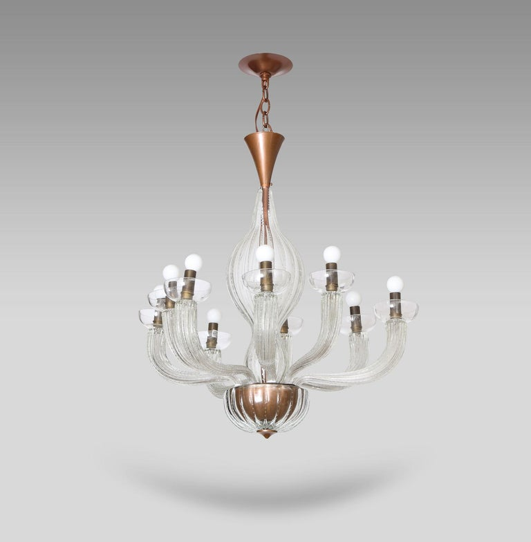 Rare 9-arm chandelier by Carlo Scarpa for Venini. Clear-colored textured glass fixture with brass mounts and gilded metal. Nine arms, each supporting a simple glass bobeche and fitted with a standard candelabra socket. This fixture has been UL