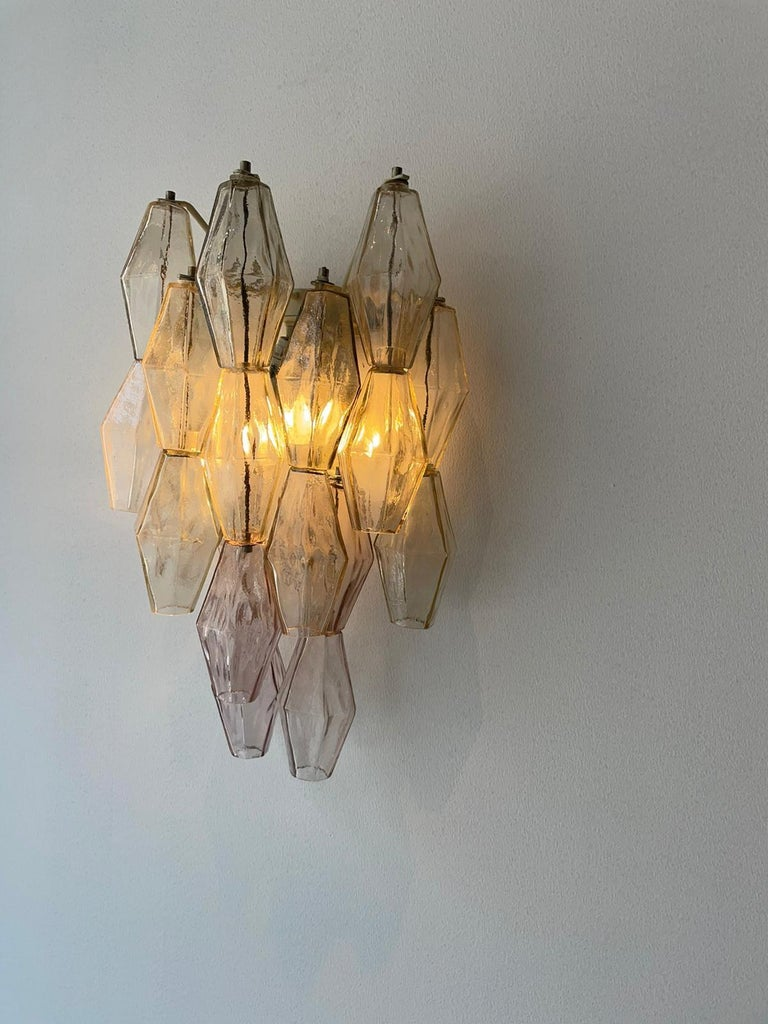 Beautiful pair of polyedral wall lamp in murano glass by Carlo Scarpa, manufactured by Venini, Italy, 1980. Diffusers elements are in polyhedral glass and lacquered metal structure.  They give a warm and pleasant light.  Scarpa asserted himself