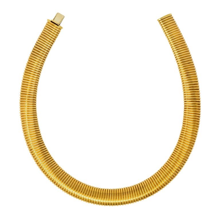 Tubogas style necklace designed as a wide, deeply ridged collar  With a polished finish  Completed by concealed clasp  Signed Weingrill with assay marks for Verona Italy and maker's mark for Carlo Weingrill  Stamped 750 for 18 karat gold  Circa: