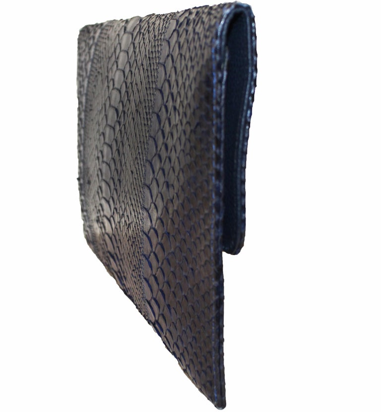 Carlos Falchi blue python clutch bag that includes a silver tone chain.  Blue python snakeskin clutch bag with magnetic snap closures under front flap and detachable silver-tone chain strap. This clutch is lined with blue embossed leather at flap