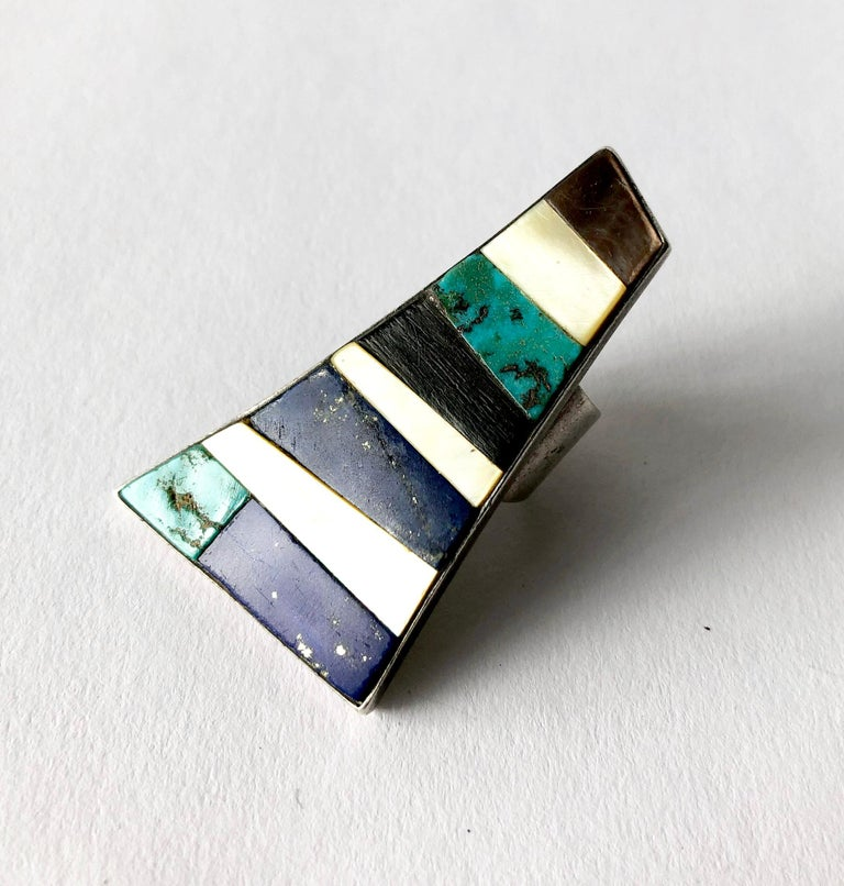Carmelo Patania turquoise, ebony, lapis lazuli and shell mosaic layered in a trapezoidal frame of sterling silver.  Ring is a finger size 6.5 to 6.75.  Face of the ring measures 2 1/4