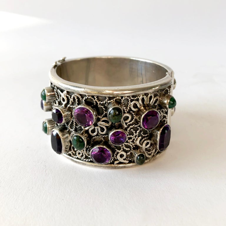 Wide, hinged bangle cuff bracelet encrusted with faceted amethyst and green gemstones created by Carmen Beckman of Mexico.  Bracelet measures 1.625