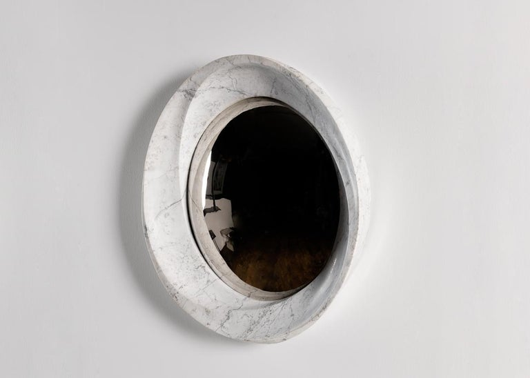 This sculptural mirror features a frame of lush marble with three inward spiraling ridges, the mutual vanishing point of which is a convex mirror of aluminum set within. The piece is one of the finest of a line of contemporary works that