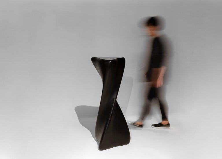 This sculptural hand carved pedestal is part of a line of contemporary furniture designed by blending digital technology with fine traditional craftsmanship. Carved of mahogany, the pedestal twists, turning 180 degrees from top to bottom, engaging,