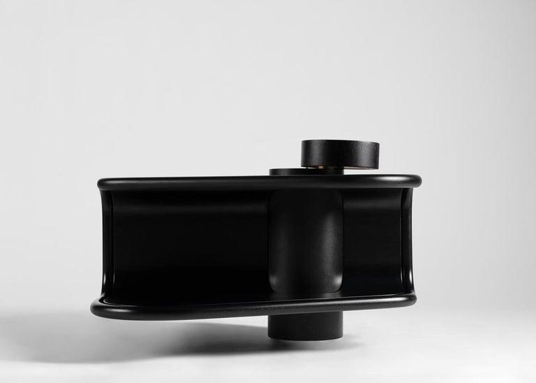 This sculptural coffee table is part of a new line of contemporary furniture designed by blending digital technology with fine traditional craftsmanship. Carved from several pieces of ebonized wood, this piece boasts two tiers, extending out from