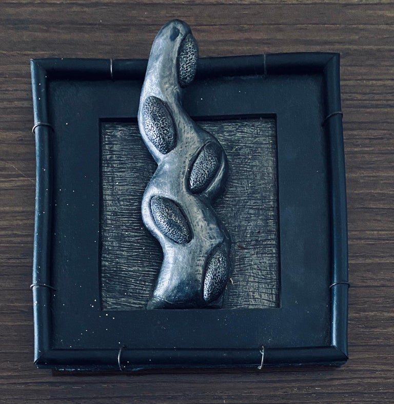This is a wall sculpture of a protruding abstract organic appendage form. They are in the form of Surrealist fantastic flora and fauna. It is from her 1990-1995 series called tondos & squares. This is a mixed media sculpture composed of