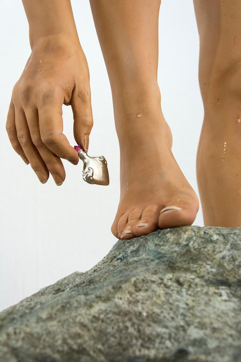 Rendered in hyper-realistic detail -- from mink hair eyelashes to simulated drops of water on ultra smooth skin -- the figure of a female swimmer bends to retrieve a small bottle. This work by American sculptor Carole Feuerman is number 3 in an
