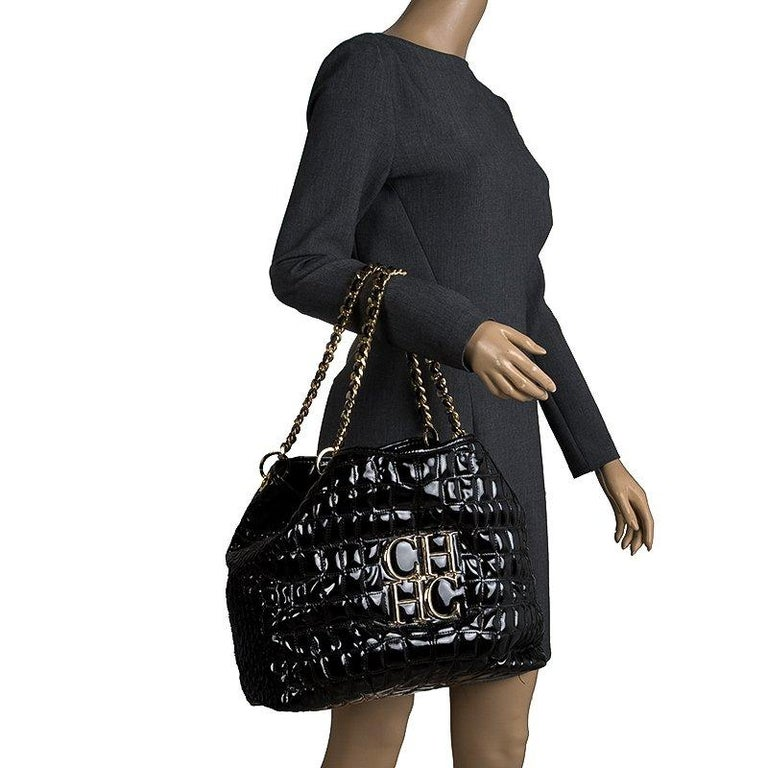 Embrace luxury with this rich black tote from the house of Carolina Herrera. The impeccable tote in patent leather bears an eye catching brand logo plaque at the front exterior. With an interwoven leather and chain strap, the tote opens to a wide