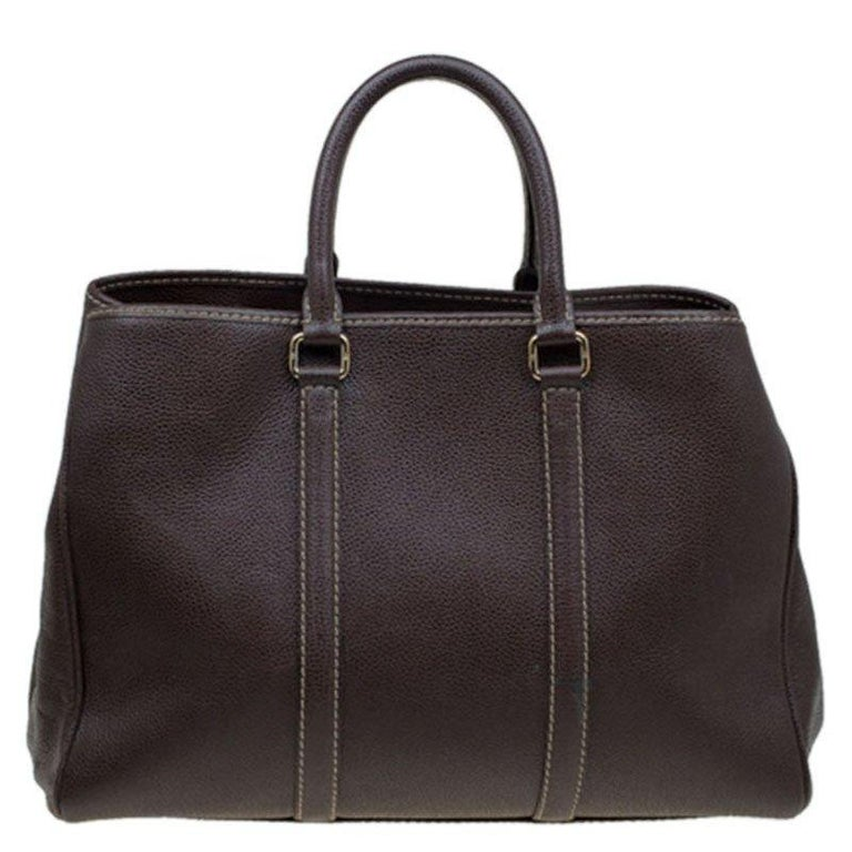 Carolina Herrara has been delivering functional, elegant designs. This dream tote from CH is made with monogrammed brown leather. It features gold-tone hardware, and two rolled handles. The zipped closure opens to a fabric-lined interior with two