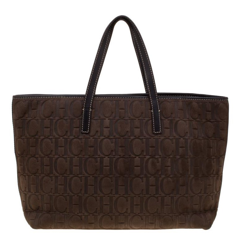 Carolina Herrera brings you this tote that is a perfect balance of elegance and practical utility. It is crafted from Monogram embossed nubuck and leather in a brown hue. It has a well-sized Alcantara interior and the bag is completed with two top