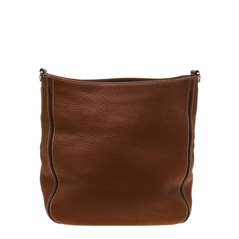 This Messenger bag comes in the shade of brown from the fashion house of Carolina Herrera. Lined from fine fabric, the interiors are spacious for you to house more than your essentials. This piece features a detachable shoulder strap with brand logo