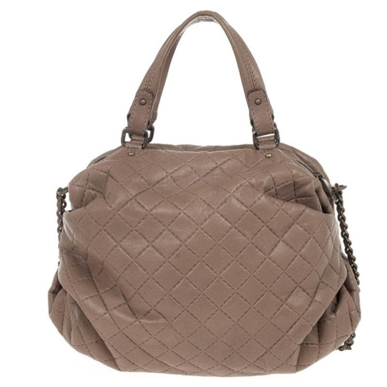 Add a touch of lady-like polish to a look with this Brown Quilted Convertible Tote. This Carolina Herrera tote is crafted from quilted brown leather and features double chain-link and leather handles. It is accented with a front Carolina Herrera