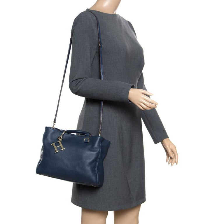 This stunning navy blue handle bag is from the house of Carolina Herrera. Crafted from leather, and lined with fabric on the insides, the bag features dual rolled top handles, a gold-tone logo charm, protective metal feet, and a detachable shoulder