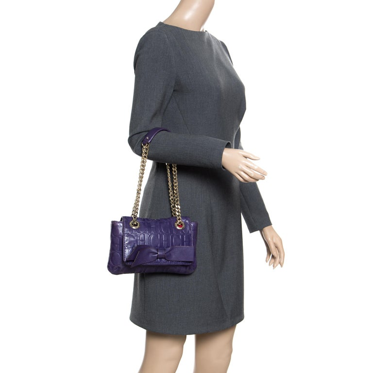 This Audrey bag from Carolina Herrera is styled with a bow detail on the front. It is crafted with signature monogram leather in a pretty purple color and a flap top that leads to a fabric-lined interior with a side zip pocket. The bag also features