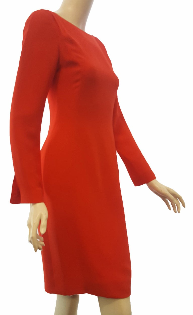 Carolina Herrera red crepe dress with long sleeves and slits at the cuffs is perfect for the holidays and winter parties!.  At the shoulders 3 small pleats on each side add texture to the padded shoulders.   This elegant but simple dress can be