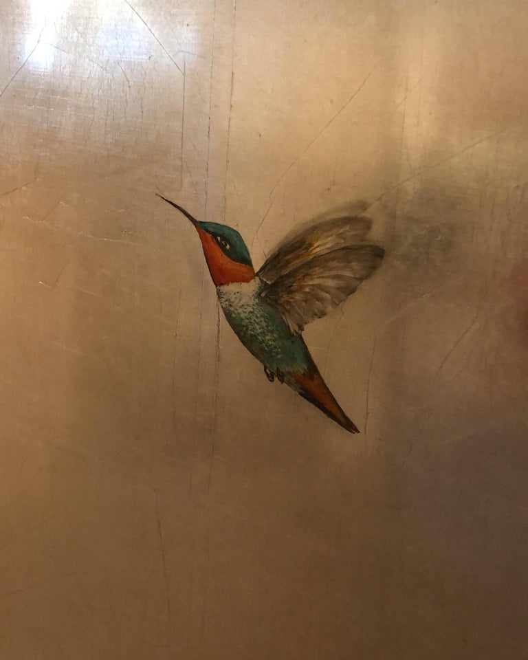 A wonderful composition of one of Reynolds' most iconic subjects, hummingbirds. This piece depicts three multicolored hummingbirds mid flight on a metallic silver surface. Reynolds encases the piece with layers of silver leaf foil and then paints