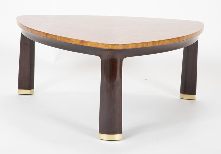 A burled triangular top coffee table rising from three walnut legs tipped with brass caps. Designed by Edward Wormley for Dunbar, circa 1955.