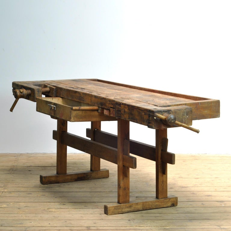 This antique workbench has two built-in wooden vices screws and a recessed tray where the carpenter would put his tools. It was manufactured around 1900. Made from oak. Beautiful patina after years of use. Really nice details in the contruction. The