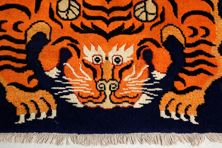 Beautiful and well colored Tibetan carpet in wool knotted by hand with cotton warp and in good condition, end of the 20th century. The symbol of the Tibetian Tiger: It was very common in antiquity and is the lord of all earthly creatures. It is
