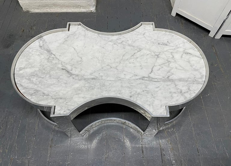Carrara marble and chrome two-tier coffee table.
