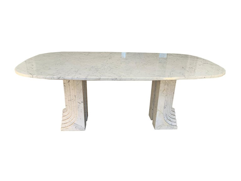 Beautiful and rare dining room table attributed to Carlo Scarpa, 1970s. The table is made of a marble top with a shape between an oval and a rectangle and is set on two marble feet.  Magnifique et rare table de salle à manger attribuée à Carlo