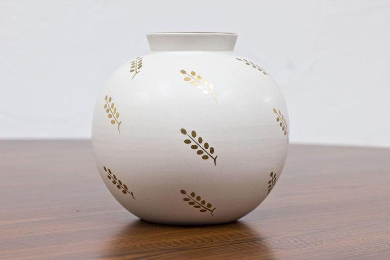 Spherical round vase designed by Wilhelm Kåge in Sweden during the 1940s.  Manufactured at Gustavsberg,  Made from white Carrara glaze with gold-colored leave pattern.  Model number 1042.  Stamped on bottom.