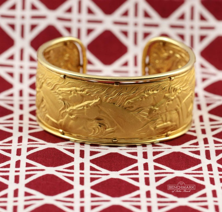 An 18 karat yellow gold bracelet framed in high polish gold, with seven galloping horses in the center. Masterfully textured and with great relief, the horses appear to gallop. Measuring 1 1/8 inches wide it will comfortably fit wrists up to 6 1/2