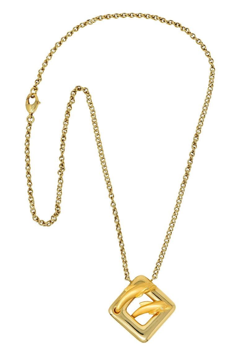 Curb chain necklace centers a brightly polished cushion shaped station  Featuring two matte finished and highly rendered dolphins with diamond accent eyes  Completed by a lobster clasp  Station and chain are stamped 750 for 18 karat gold  Both have