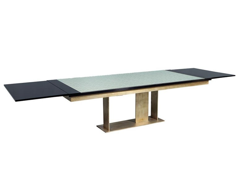 Carrocel custom modern glass top dining table with brass base. Custom-made dining table, styled with a modern brass base flowing into a textured glass top, glass is smooth on top, texture is underneath. Table has black lacquered accent ends with