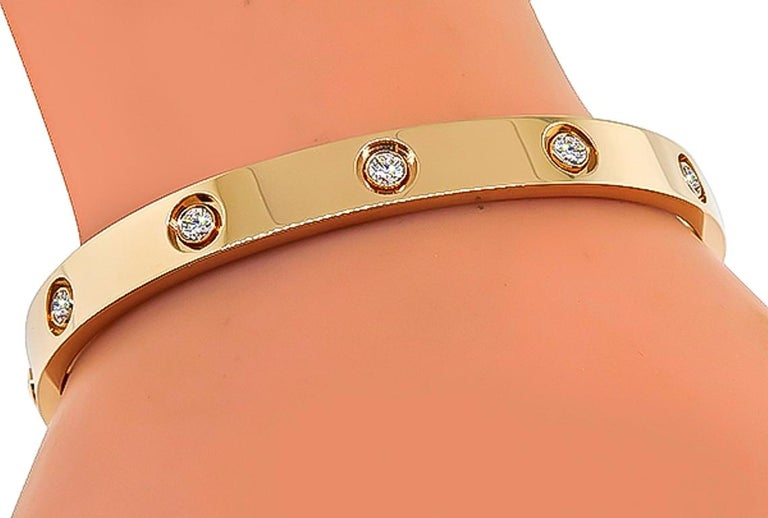 This amazing 18k rose gold love bangle by Cartier is set with 10 sparkling round cut diamonds that weigh approximately 0.95ct. The bangle is size 17 and weighs 30.7 grams. It is signed Cartier 17 Au750 APS007 and comes with a screwdriver. Inventory