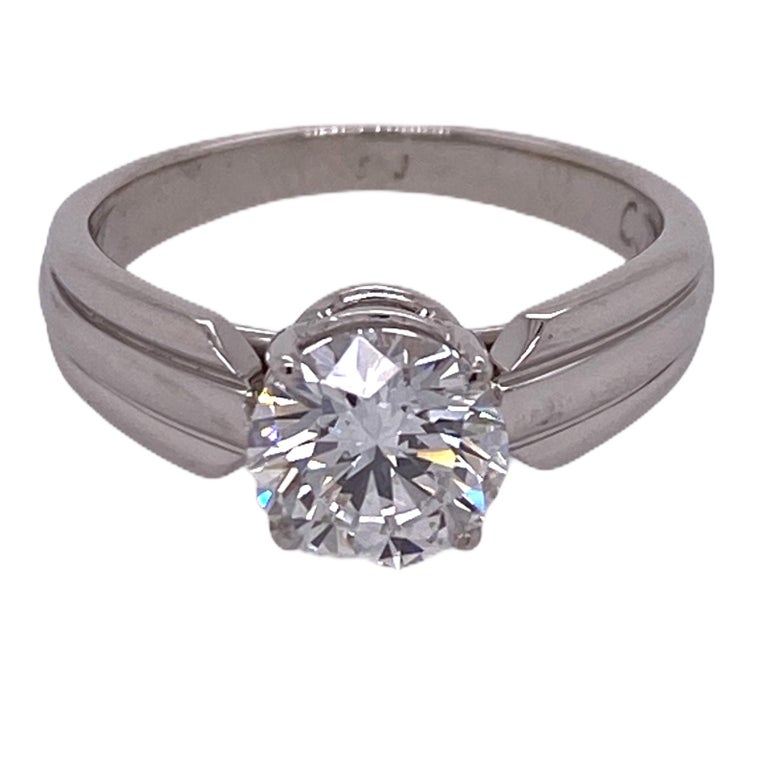 Stunning solitaire diamond engagement ring by Cartier. The round brilliant cut diamond weighs 1.51 carats and is graded E color and VVS2 clarity by the GIA. The certificate and appraisal are in photos. The platinum mounting measures 5mm in width, is
