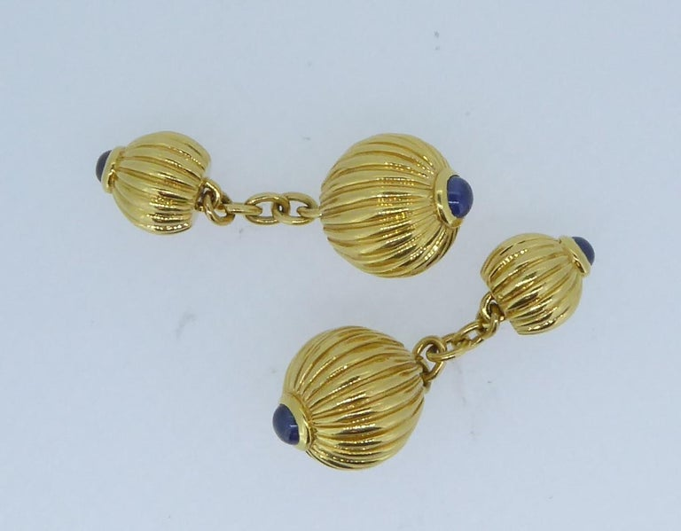 Pair of Cartier 18 Carat Yellow And Blue Sapphire Melon Bead Cufflinks. The four yellow gold ridged each topped with a cabochon blue sapphire. Signed