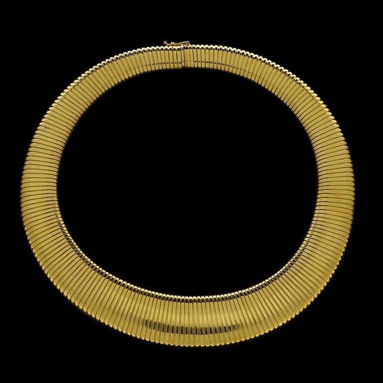 """18 Carat yellow gold signed Cartier, stamped K18 and numbered 548 to the tongue 16"""" long, centre front 0.9"""" wide, centre back 0.5"""" 89 grams  A wide flattened gas-pipe link necklace by Cartier c.1950s, the highly flexible necklace of gently tapering"""