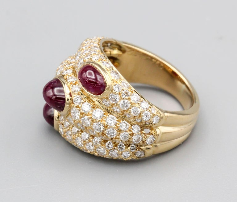 Fine 18k yellow gold ring with pave set diamonds and set with three rich ruby cabochon stones, by Cartier, circa 1990s. The design of the ring is made to look like three rings stacked on top of one another with each ruby cabochon slightly offset