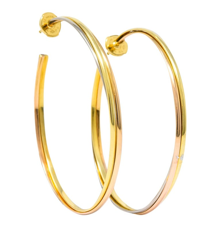 Large hoop style earrings comprised of three segments of intertwined yellow, white, and rose gold  With a high polish finish  Completed by posts and la pousette backs  From Cartier's Trinity collection  Fully signed Cartier with 750 stamp for 18