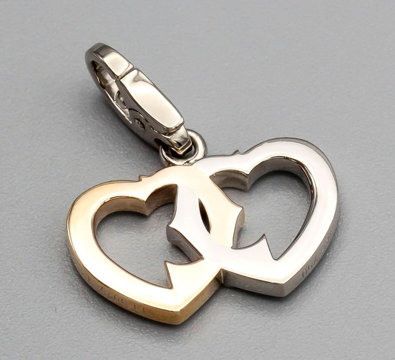 Fine 18k yellow and white gold interwined double heart logo charm by Cartier.  Hallmarks: Cartier, 750, reference numbers, maker's mark.
