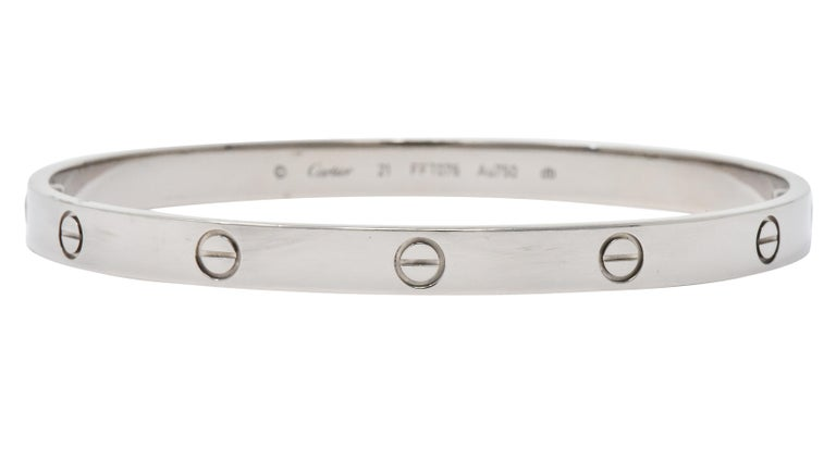 Bangle style bracelet with repeating Cartier Love symbol  With two screws to open the bangle completely  From the highly coveted Love collection  Fully signed Cartier, numbered, stamped 21, Au 750 and db  Accompanied by original box and