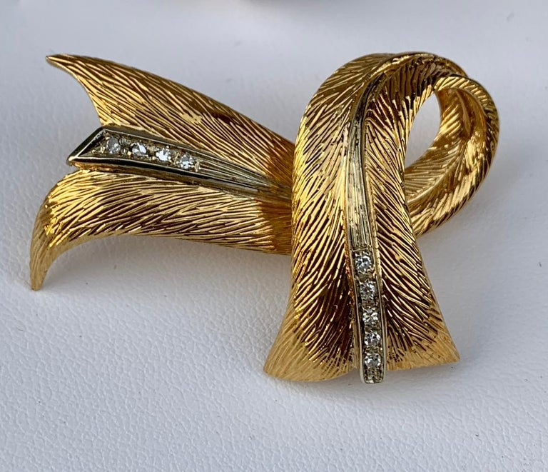 Very flowing, three dimensional, stylized ribbon or scarf design brooch pin by esteemed French designer, Cartier, is depicted in 18 karat yellow gold accented with rows of white diamonds down the middle of each side. Brooch could also be worn as a