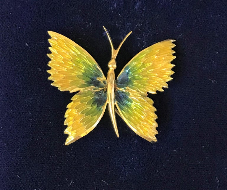 This hard to find Cartier brooch has beautiful green and blue colors that would compliment any outfit! Cartier 18 karat yellow gold brooch Enamel top with blue, green and yellow colors and gold on wings Stamped CARTIER, 18K and 20325 Pin goes from