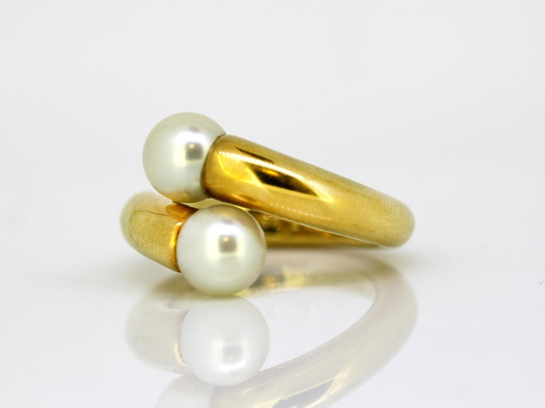 18k gold ladies ring with two natural freshwater pearls.  Designer: Cartier  Made in France Circa 1990's  Fully hallmarked.   Dimension -  Ring Size : 2.6 x 2.4 x 1.5 cm  Finger Size : (UK) = K (US) = 5 1/2 (EU) = 50 1/4  Weight : 15 grams
