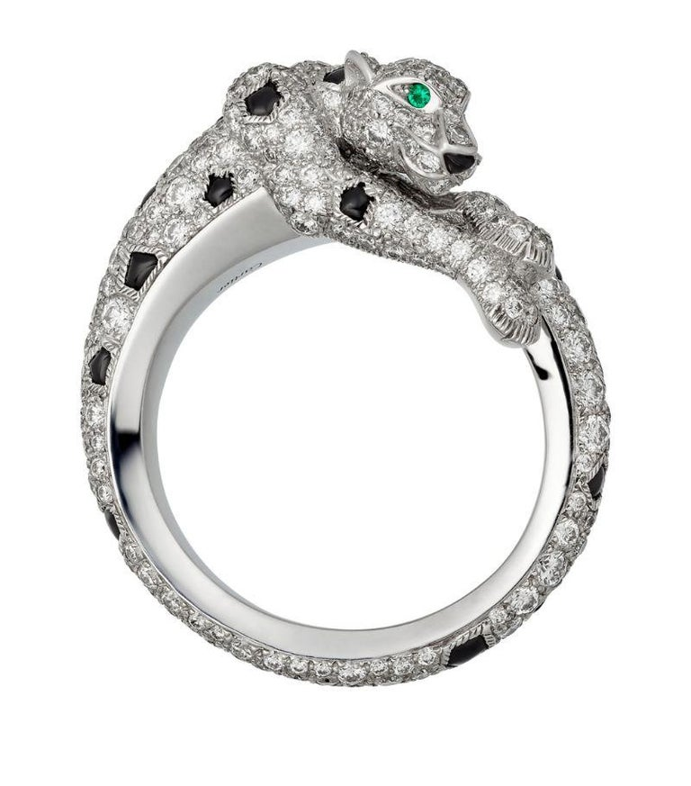 Panthere de Cartier ring in 18K white gold. Detailed with gleaming emeralds for eyes and sparkling diamonds and onyx stones depicting its majestic coat. 264 brilliant-cut diamonds totaling 1.66 carat. Width of the pattern: 8.7 mm. Ring size 53 US