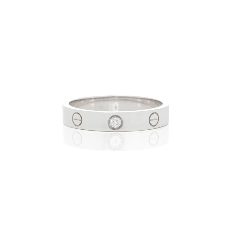 This Ring by Cartier is from their Love Collection and features One Round Brilliant Cut Diamond mounted in an 18k White Gold band. Ring Size UK Q 1/2, EU Size 59, USA Size 8 1/2. Complete with Original Cartier Box and Warranty Certificate. Our Xupes