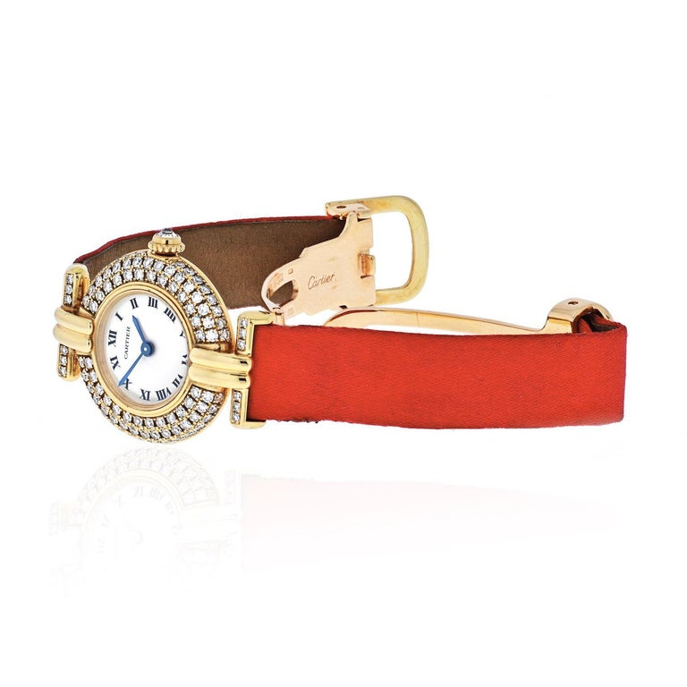 Cartier ladies diamond watch on a bright pink satin strap.  18 kt., quartz, centering a circular off-white dial with black Roman numerals and blued steel hands, within a pavé-set case and lugs of 102 single-cut diamonds ap. 1.80 cts., inverted